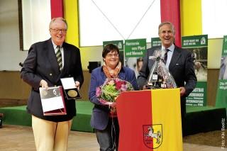 Ein Dankeschön für unermüdliches Engagement in der Förderung der Bodenarbeit: Sally Mauson wurde von FN-Vizepräsident Dieter Medow (li.) und Klaus Bergjohann mit der Dieter-Graf-Landsberg- Velen-Medaille in Bronze ausgezeichnet.